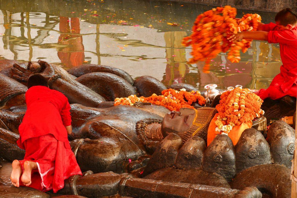 Monaci che vestono la statua di Vishnu